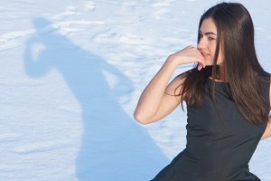 Portrait attractive young brunette girl touches her face with hand on a snowy background and shadow