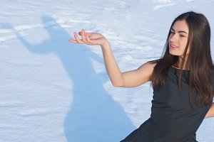 Portrait attractive young brunette girl on a snowy background with shadow