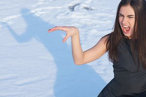 Portrait attractive screaming young brunette girl on a snowy background with shadow
