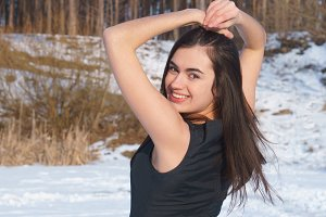 Young brunette girl happy smiling in a black dress crossed hands up on the snow forest background