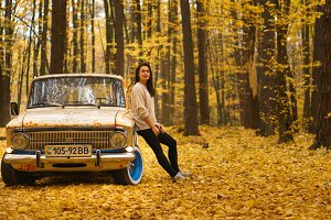 Young brunette girl stands near a retro car in an autumn forest