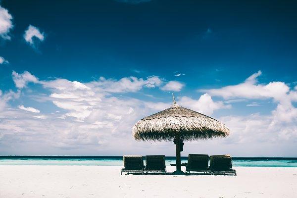 Straw umbrella and sunbeds on a san…