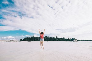 Girl jumping on a sandy beach. Fun t