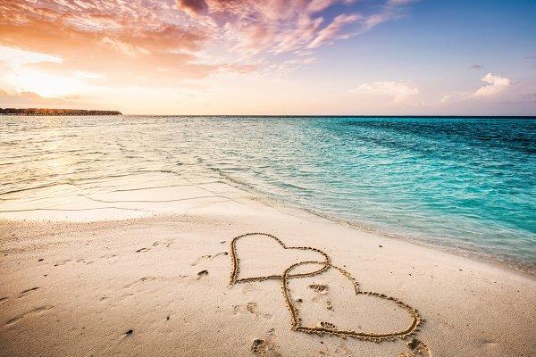 Two hearts drawn on a sandy beach b…