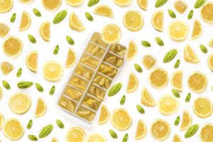 Ice cubes with lemons on white backg