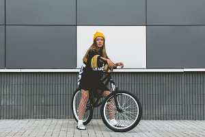 Girl posing on a street bicycle