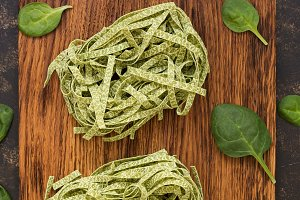 Raw green pasta with spinach on a cu
