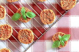 Mini pizas on checkered tablecoth.