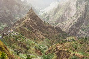 Mountain peaks in Xo-Xo valley of Santa Antao island in Cape Verde. Landscape of many cultivated plants in the valley between high rocks. Arid and erosion mountain peaks under hot sun light