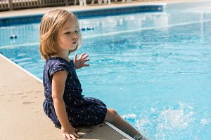 Small girl kicking the water in a swimming pool