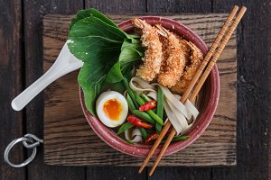 Top view af noodle soup with fried prawns, egg and pak-choi