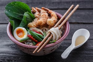 Japanese noodle soup topped with tempura shrimps, egg and greens, close view