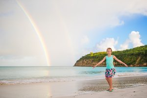 Happy little girl backgound the beautiful rainbow over the sea. Beautiful rainbow on caribbean beach