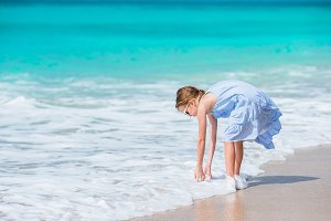 Adorable little girl in the shallow water. Beautiful kid washing her hands in the wave