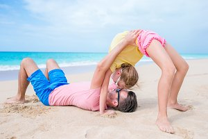 Father and little girl at beach having a lot of fun. Sporty kid makes sport exercises on the seashore