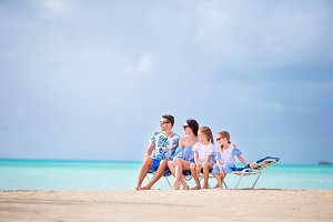Young family on vacation at sunbeds on white beach