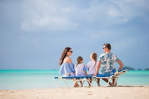 Young family on vacation. Parents and kids on sunbed enjoy the sea view