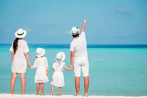 Young family of four in white on tropical beach. PArent with two little kids looking at the sea