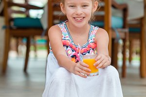 Adorable little girl with juice at outdoor cafe