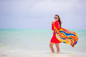 Young beautiful woman on tropical seashore. Happy girl in beautiful dress background the sea