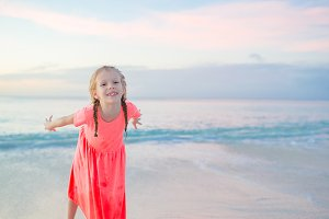 Adorable little girl at beach having a lot of fun in the evening. Happy kid looking at camera background beautiful sky and sea