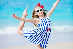 Active little girl at beach having a lot of fun. Sporty kid making the sports items on the seashore