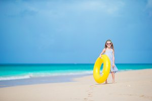 Adorable girl with inflatable rubber circle on white beach ready for swimming