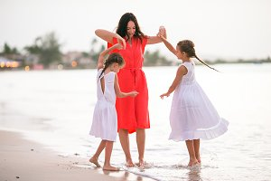 Family of mom and kids have a lot of fun on white beach