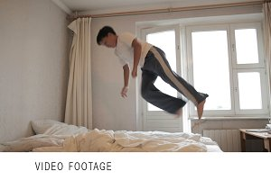 Teenager jumps on the bed