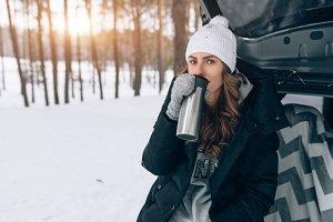 woman drink hot tea in winter forest