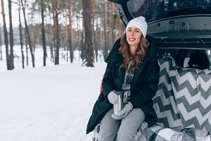 smiling woman car winter forest