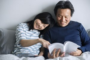 Asian couple reading a book
