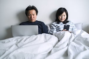 Asian couple using digital devices