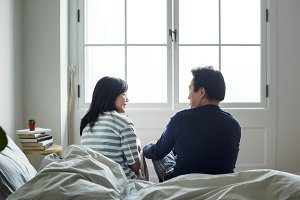 Asian couple talking together in bed