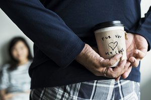 Man brings a cup of coffee for wife