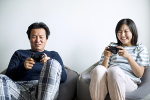 Asian couple playing video game