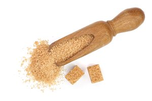 brown sugar in wooden scoop isolated on white background. Top view. Flat lay