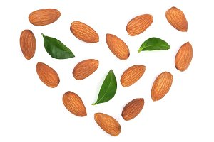 almonds in the shape of a heart with leaves isolated on white background. Top view. Flat lay pattern