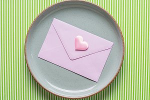 Gray dish with pink envelope on gree