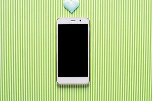 Heart and smartphone on green backgr