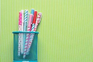 Colorful girlish pens on green backg