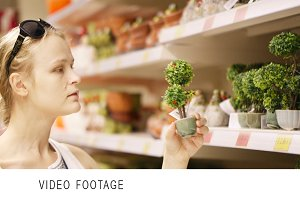 Attractive woman choosing potted