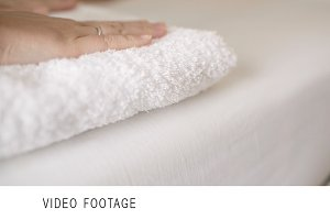 Woman smoothing a fresh white towel
