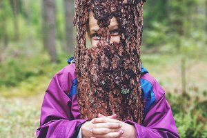 Funny girl with a piece of tree bark