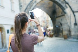 a woman tourist in the center of Prague taking a photo by the phone