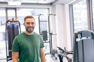 Smiling man surrounded by gym equipm