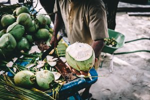 Man handing in a green coconut. Trad