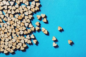 Wooden hearts laying on blue backgro