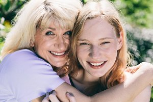 Older woman hugging young woman