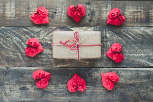 Red paper hearts with gift on wooden
